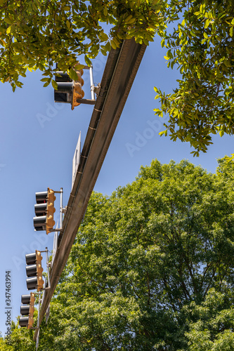 Photo Row of stoplights on a traffic arm, seen from below, blue sky and green trees, v