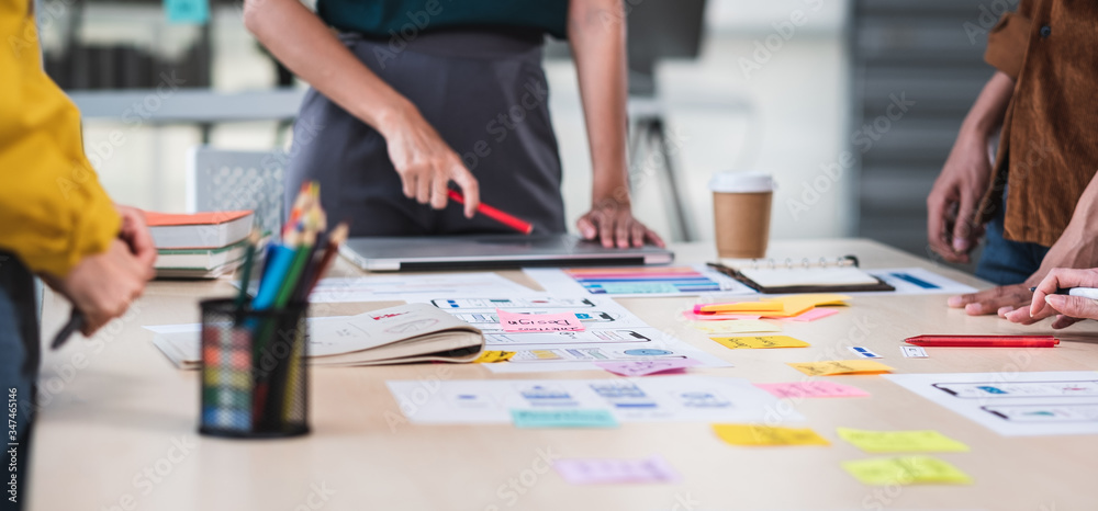 Fototapeta Close up ux developer and ui designer brainstorming about mobile app interface wireframe design on table with customer brief and color code at modern office.Creative digital development agency.panning
