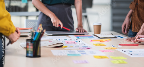 Obraz na plátně Close up ux developer and ui designer brainstorming about mobile app interface wireframe design on table with customer brief and color code at modern office