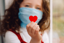 Cute Preschool Little Girl In Protective Medical Masks Sitting On Sill, Holding Red Heart A Way To Show Appreciation And To Thank All Essential Employees During Covid-19 Pandemics. Selective Focus