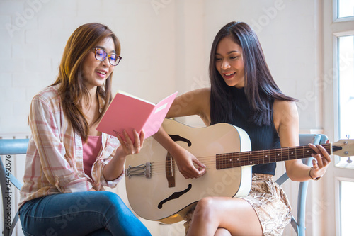 Two beautiful Asian women Playing guitar and singing together happily at home Tablou Canvas