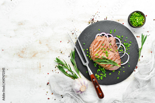 Fototapeta Juicy roasted veal steak with rosemary and spices. Top view. Free space for your text. obraz