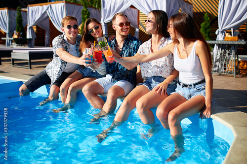 Group of friends having fun at poolside party clinking glasses with fresh cocktails sitting by swimming pool on sunny summer day Canvas Print