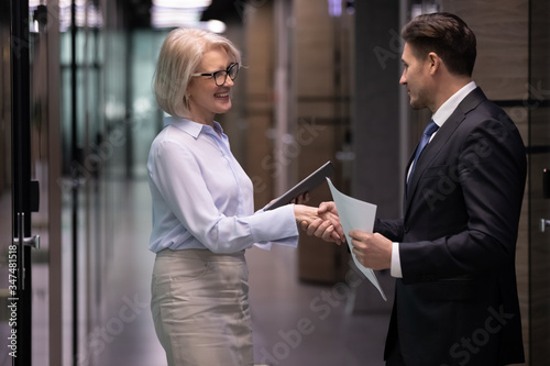 Photo Mature and young businesspeople stand in office hall shake hands get acquainted greeting each other