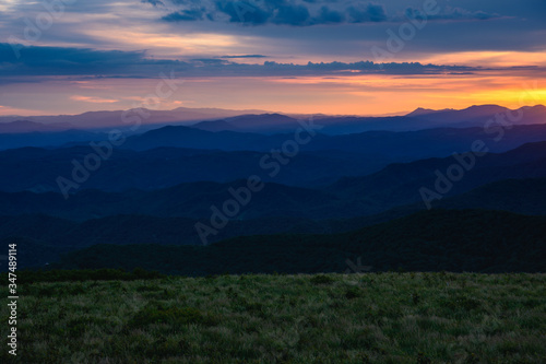 Sun Sets Behind Mountain Layers and Grassy Field