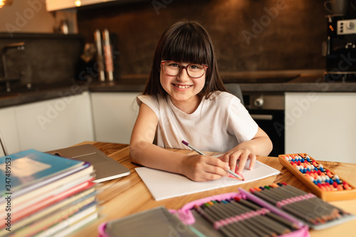Vászonkép Happy schoolgirl does homework at home