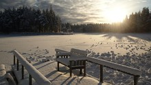 Snow Covered Bench At Park During Sunset In Winter