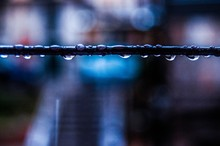 Close-up Of Water Drops On Railing Against Blurred Background