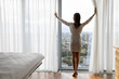 Rear full length of woman opened curtains enjoys big picturesque city standing barefoot on warm heated floor near panoramic window enjoy urban view, climate control at home, welcoming new day concept