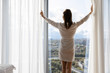 Rested female in white night robe wake up opens curtains enjoys big city and sunny weather, rear view. Welcoming of new day, good morning, modern warm hotel bedroom, luxury apartments owner concept