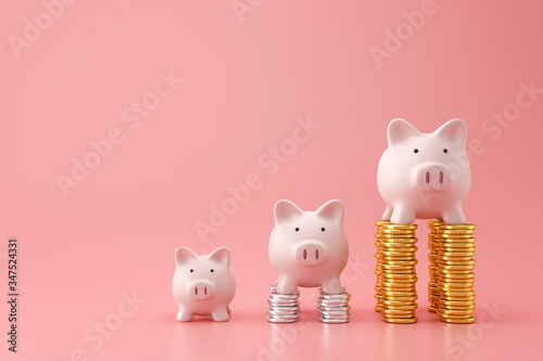 Photographie Piggy bank and golden stack coins of three level graph on pink background with saving money concept
