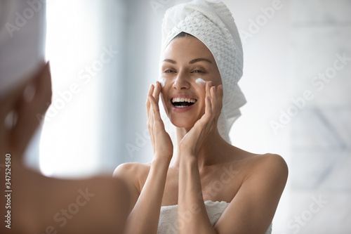 Fototapeta Without make-up face of 30s woman touch face with fingers apply caring about skin uses moisturiser creme. Morning routine, grooming, personal care, skincare beauty treatment natural cosmetics concept obraz