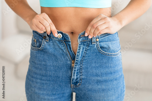 Fototapeta Unrecognizable Girl Wearing Small Jeans After Gaining Excess Weight, Cropped obraz