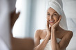 canvas print picture After shower body and head wrapped in towel 35s woman looks in mirror touches moisturized soft healthy face skin feels satisfied enjoy spa cosmetics treatment procedure, morning care hygiene concept
