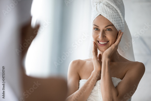Fototapeta After shower body and head wrapped in towel 35s woman looks in mirror touches moisturized soft healthy face skin feels satisfied enjoy spa cosmetics treatment procedure, morning care hygiene concept obraz na płótnie