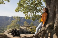 Woman Leaning On Tree Against Mountain