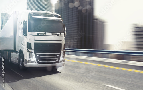 Fototapeta White truck moving fast on the highway with a modern city in the background obraz
