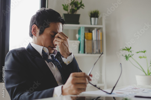 Obraz na płótnie tired asian young businessman feeling stressed and taking off eyeglasses feels e