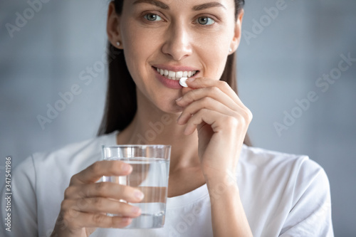 Fototapeta Close up image young adult beautiful 35s woman smiles takes pill holding glass of water, concept of minerals and vitamins for female, hair skin nail care dietary supplement, daily dosage of medication obraz na płótnie