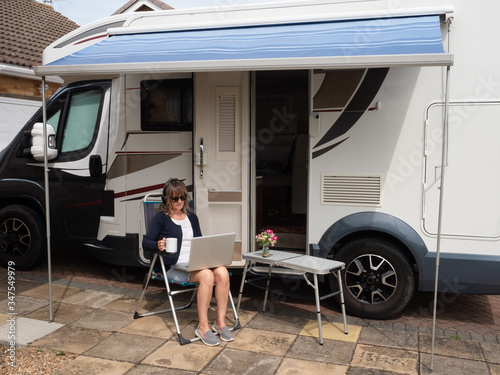 Fotomural A lady motor home owner is parked on her drive unable to travel due to lockdown