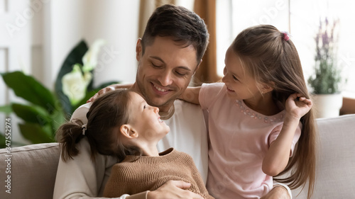 Happy loving young father hugging two little daughters close up, family enjoying tender moment, sitting on couch at home, smiling dad and preschool children spending free time together