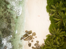 Tropical Beach With Palm Trees, Sandy Beach And Typical Granite Rocks And A Woman In Red Bikini From High Above, Birds Eye View, Drone Picture.