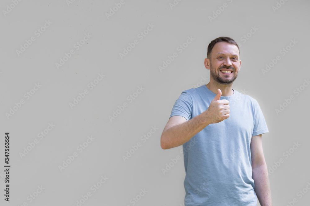 Fototapeta Uśmiechnięty mężczyzna na szarym tle, pokazujący dłonią gest ok, uniesiony w górę kciuk