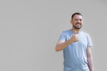 Uśmiechnięty mężczyzna na szarym tle, pokazujący dłonią gest ok, uniesiony w górę kciuk