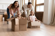 Happy parents playing with children in new apartment living room, two cute little daughters sitting in cardboard boxes, laughing mother and father pushing, family celebrating moving day
