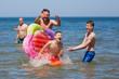 Zabawa w morzu, roześmiana rodzina chlapie się wodą, chłopiec spada z kolorowego materaca