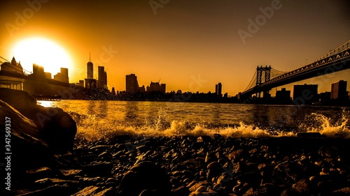 Fotografering Silhouette Manhattan Bridge Over East River Against Clear Sky During Sunset