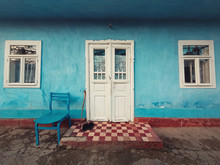 Walking Stick, And A Pair Of Old Shoes And A Chair On The Doorstep Of An Aged House. Traditional Rural Building Facade. Blue Lime Painted Walls, White Colored Door And Windows. Vintage Home Details.