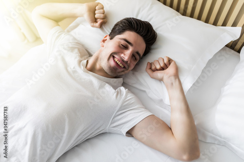 Fototapeta Young handsome happy man waking up on bed, top view obraz na płótnie
