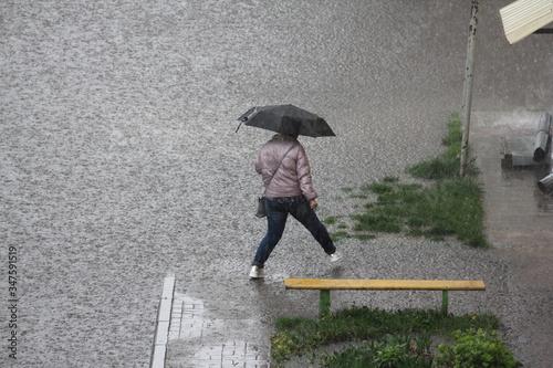 A woman under an umbrella walks near a house with a damaged drainpipe on the Ban Tapéta, Fotótapéta