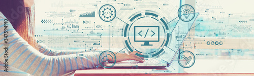 Fototapeta Web development concept with woman working on a laptop in brightly lit room obraz