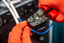 Hands In Orange Insulating Gloves Work With Crimping Pliers And Cables. Horizontal Orientation.