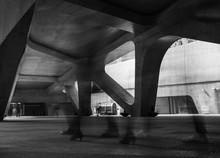 Group Of Blurred People Walking Under Bridge