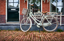 Volendam Amsterdam Netherlands. White Retro Bicycle With Basket At Street With Brick Red House And Wooden Bench.
