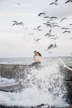 Many Gulls Are Flying Under The Young Couple Which Sitting On The Promenade At The Seaside.