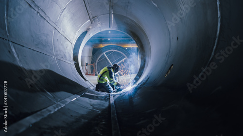 Fotomural Professional Heavy Industry Welder Working Inside Pipe, Wears Helmet and Starts Welding