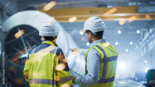 Fotografía Two Heavy Industry Engineers Stand in Pipe Manufacturing Factory, Use Digital Tablet Computer, Have Discussion
