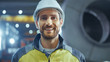 Portrait of Smiling Professional Heavy Industry Engineer / Worker Wearing Safety Uniform and Hard Hat. In the Background Unfocused Large Industrial Factory