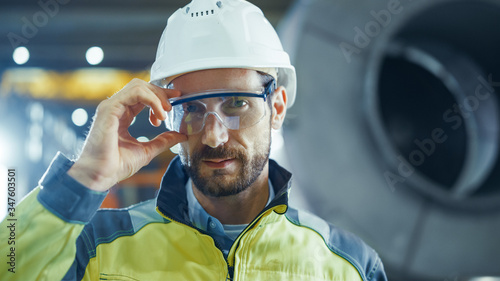 Fotografering Portrait of Smiling Professional Heavy Industry Engineer / Worker Wearing Safety Uniform and Hard Hat Putting on Glasses