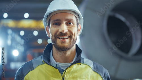 Obraz Portrait of Smiling Professional Heavy Industry Engineer / Worker Wearing Safety Uniform and Hard Hat. In the Background Unfocused Large Industrial Factory - fototapety do salonu
