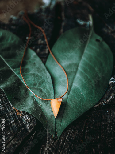 Beautiful handmaded necklace (amulet) with shining blue epoxy with green leafs on background - moody folk style photo Wallpaper Mural