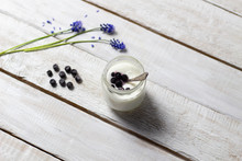 Home Made Yogurt In Glass Jar With Blueberry And Spoon  On White Wooden Background With Grape Hyacinth