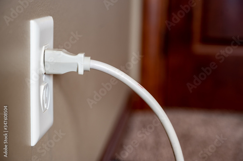 Fotomural Side view of white power cord plugged into a white wall outlet