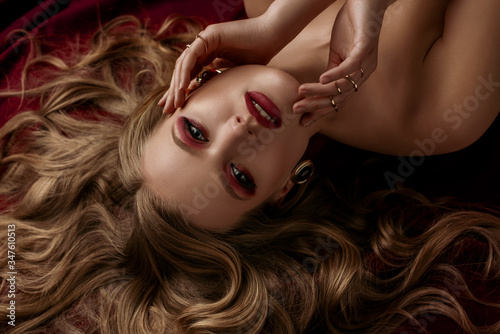 Obraz na plátně Beautiful woman with luxury blond hair, glow skin, dark red eyes and lips makeup, wearing a lot of golden rings, stylish earrings, posing, laying on sheets