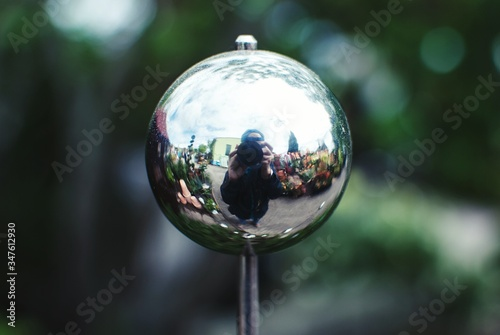 Fotografie, Obraz Reflection Of Person Photographing With Camera In Metal Ball