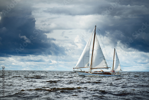 Foto Old expensive vintage wooden sailboat (yawl) close-up, sailing in an open sea